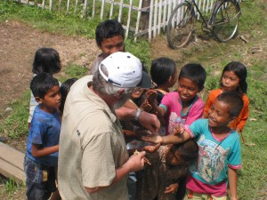 CMAT physician Dr. Dave Ratcliffe from Comox, B.C. hands out treats for the child survivors of the Tsunami in Meuloboh, Indonesia. (January 2005)