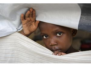 A child peeks through the walls of his makeshift home in a displaced persons camp in Port au Prince, Haiti.