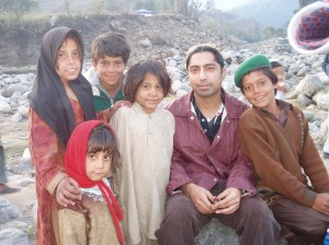 Dr. Omar Elahi sits with local children in Balakot, Pakistan.