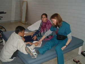 Joan teaching local P.T., Rajeesh specific spinal cord injury assessment with S.J. (20 y/o from Muzaffarabad area with complete spinal cord injury).