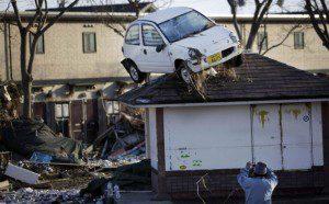 A man takes a picture in Sendai, northern Japan, of the aftermath of the tsunami. (Photo Courtesy Junji Kurokawa/AP)