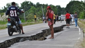 People walk along a damaged road in the province of Bohol on Tuesday, October 15. (AP Photo)